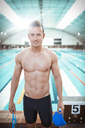 Swimmer standing at poolside - CAIF03803