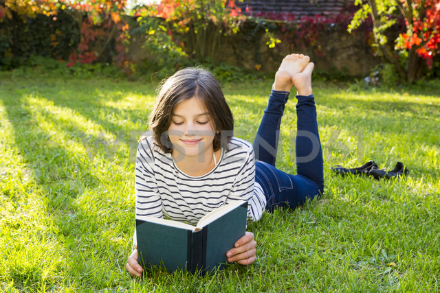 Smiling girl lying on meadow reading a book - LVF06753