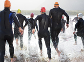 Triathletes in wetsuits running in waves - CAIF03813