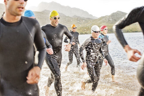 Triathletes in wetsuits walking in waves - CAIF03816