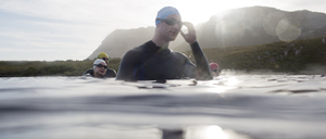 Triathletes in wetsuits standing in water - CAIF03828