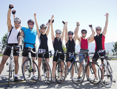 Cyclists cheering together on rural road - CAIF03834