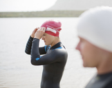 Triathletes pulling on goggles on beach - CAIF03849