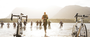 Triathletes running to bicycles on beach - CAIF03858