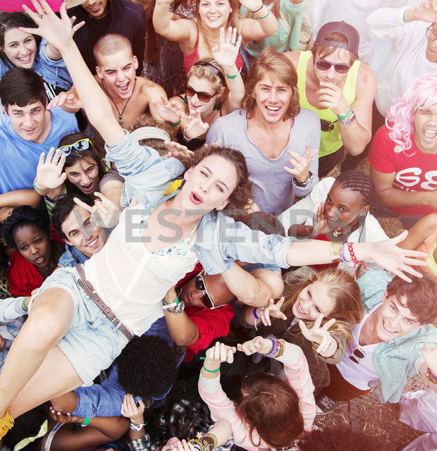 Enthusiastic woman crowd surfing at music festival - CAIF03888
