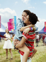 Enthusiastic couple hugging at music festival - CAIF03906