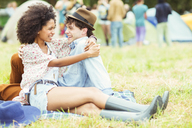 Couple hugging in grass outside tents at music festival - CAIF03918