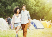 Couple walking outside tents at music festival - CAIF03924