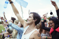 Man with water bottle cheering at music festival - CAIF03945