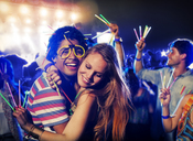 Couple with glow sticks hugging at music festival - CAIF03948