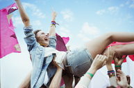 Enthusiastic woman crowd surfing at music festival - CAIF03951