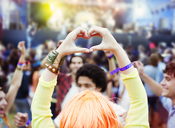 Woman forming heart-shape with hands at music festival - CAIF03960