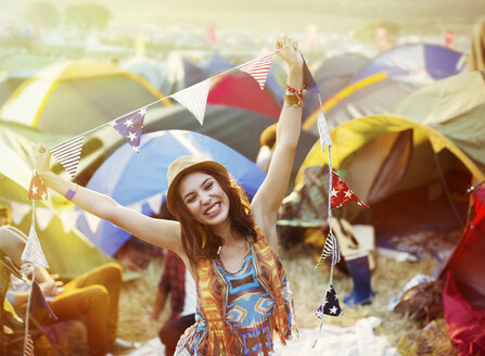 Portrait of enthusiastic woman outside tents at music festival - CAIF03969