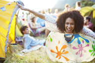 Portrait of playful woman laying on inflatable chair outside tents at music festival - CAIF03972
