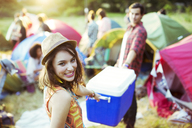 Portrait of woman helping man carry cooler outside tents at music festival - CAIF03978