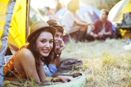 Portrait of couple laying in tent at music festival - CAIF03981
