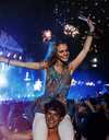 Portrait of cheering woman on manÍs shoulders at music festival - CAIF03990