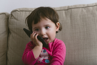 Baby girl talking on mobile phone at home - GEMF01893