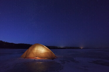 Russia, Amur Oblast, illuminated tent on frozen Zeya River at night under starry sky - VPIF00377