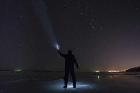 Russia, Amur Oblast, silhouette of man with blue ray standing on frozen Zeya River at night under starry sky - VPIF00380