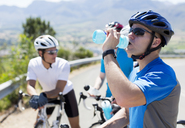 Cyclist drinking water on rural road - CAIF04054