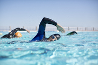 Triathletes in wetsuits racing in pool - CAIF04072