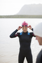 Triathlete adjusting goggles outdoors - CAIF04075