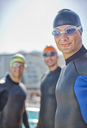 Triathletes wearing wetsuits outdoors - CAIF04078