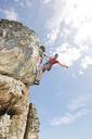 Climber scaling steep rock face - CAIF04108