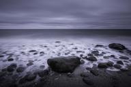 Tranquil overcast gray seascape and rocks on beach, Kalundborg, Denmark - CAIF04159