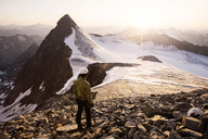 Austria, Tyrol, Stubaital, Stubai Alps, Wilder Pfaff, hiker looking to sunset, Zuckerhuetl left - CVF00230