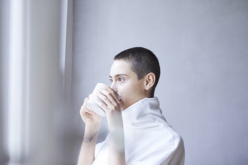 Portrait of short-haired young woman drinking from mug - FMKF04903