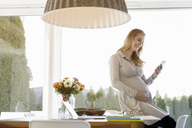 Smiling pregnant woman sitting on desk looking at cell phone - BMOF00006