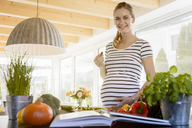 Portrait of smiling pregnant woman in kitchen at home eating cucumber - BMOF00009