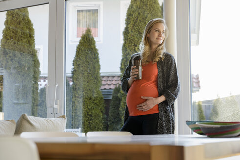 Smiling pregnant woman holding glass standing at the window at home - BMOF00021