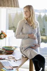 Smiling pregnant woman working at home sitting on table - BMOF00024