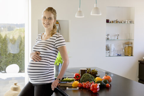 Portrait of smiling pregnant woman in kitchen at home - BMOF00027