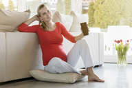 Smiling pregnant woman sitting on floor at home holding a cup - BMOF00030