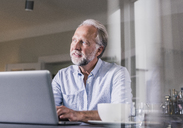 Portrait of mature man sitting at table using laptop at home - UUF12926