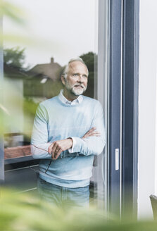 Mature man looking out of terrace door - UUF12944
