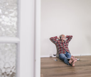 Barefoot man relaxing on the floor at home - UUF12953