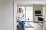 Portrait of smiling mature man leaning against door case in his apartment - UUF12959