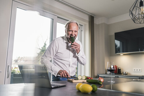 Funny mature man eating raw cougette in the kitchen - UUF12965