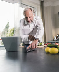 Mature man preparing food in the kitchen while using laptop - UUF12968