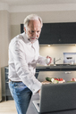 Portrait of mature man using laptop in the kitchen - UUF12971