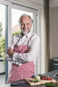 Portrait of smiling mature man with apron in his kitchen - UUF12974