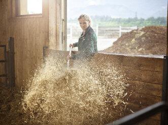 Female farmer working with straw on a farm - CVF00251