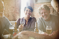 Laughing couples drinking white wine and beer at restaurant table - HOXF00002