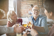 Couples toasting beer and wine glasses at restaurant table - HOXF00014