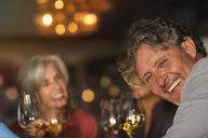 Portrait laughing senior man drinking white wine with friends at bar - HOXF00029